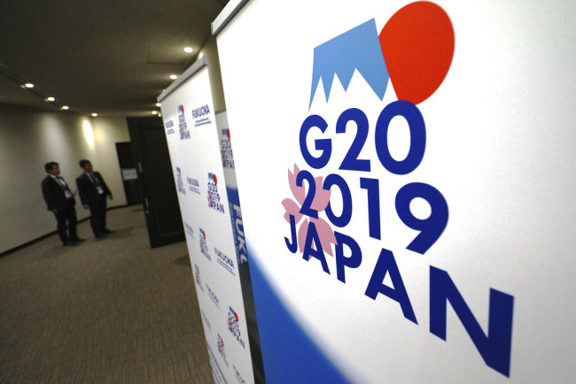 In this June 7, 2019, staff members stand near the emblem of G20 2019 Japan at the entrance of the press center of G20 Finance Ministers' and Central Bank Governors' Meeting in Fukuoka, western Japan. [File photo: AP/Eugene Hoshiko]