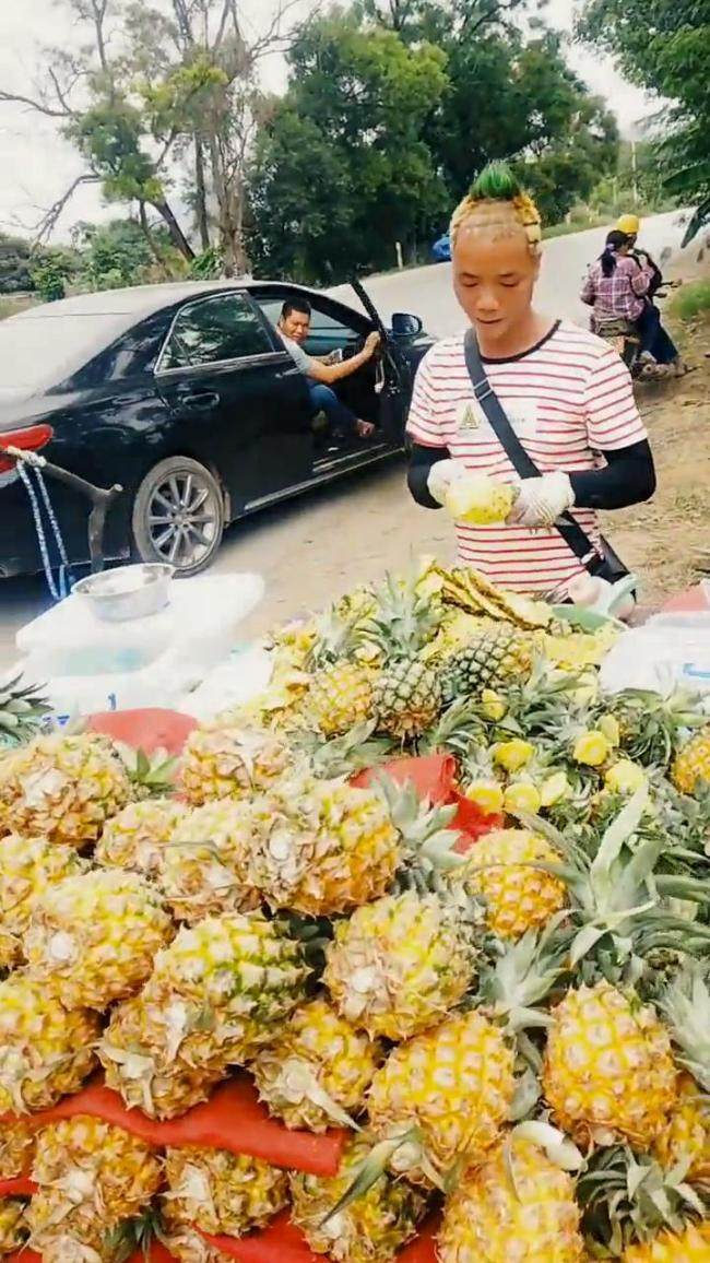 A man cut his hair(头发 tóufa) in the style of a pineapple(菠萝 bōluó) to help sell(卖 mài) the fruit(水果 shuǐguǒ) in Nanning, Guangxi Zhuang Autonomous Region, July 14, 2019. Su Changfeng has been selling pineapples for six years. [Photo: IC]