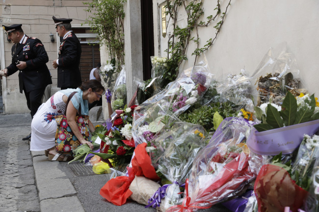 A woman leaves flowers in front of the Carabinieri station where Mario Cerciello Rega was based, in Rome, Saturday, July 27, 2019. In a statement Saturday, Carabinieri officers investigating the death Friday of officer Cerciello Rega, 35, said two American turists, both 19, have been detained for alleged murder and attempted extortion. [Photo: AP/Andrew Medichini]