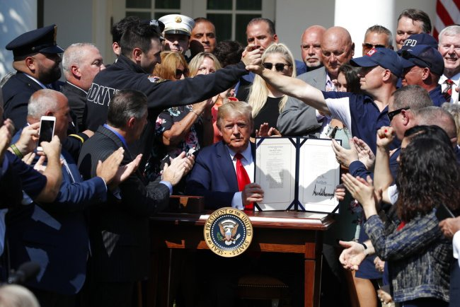 President Donald Trump holds up the signed H.R. 1327 bill, an act ensuring that a victims' compensation fund related to the Sept. 11 attacks never runs out of money, in the Rose Garden of the White House, Monday, July 29, 2019, in Washington. [Photo: AP]