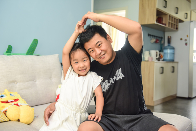 Cartoonist Cheng Peng is pictured with his daughter in Qingdao, Shandong Province on July 28, 2019. [Photo: IC]