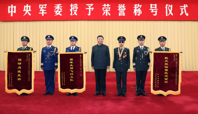 "Xi Jinping (C), chairman of the Central Military Commission (CMC), poses for a group photo with a soldier and representatives of three military units during a CMC ceremony in Beijing, capital of China, July 31, 2019. Xi has signed orders to honor a soldier and three military units. At the ceremony on Wednesday, Xi hung a medal around the neck of Du Fuguo, who was awarded the title ""Heroic Demining Soldier"", and presented him with a certificate, and went on to confer honorary banners to representatives of the three units. [Photo: Xinhua]"