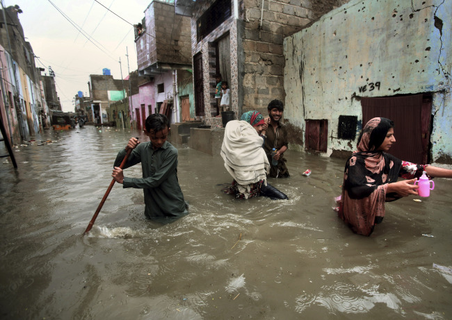 A family wades through a flooded street caused by heavy monsoon rains, in Karachi, Pakistan, Sunday, Aug. 11, 2019. [Photo: AP via IC/Fareed Khan]