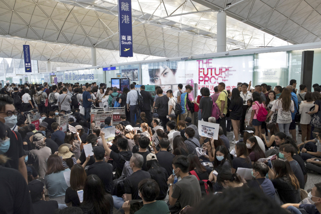 Travelers line up as protesters stage a sit-in rally near the departure gate of the Hong Kong International Airport in Hong Kong, Aug. 13, 2019. [Photo: AP/Vincent Thian]