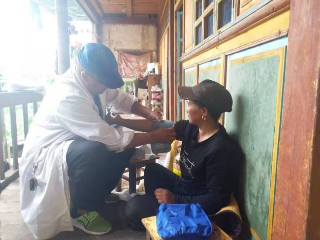 Longchen Tsodo was teaching Tashi Lhamo that had won the battle with breast cancer how to use blood-pressure meter during a recent visit. [Photo: from China Plus]