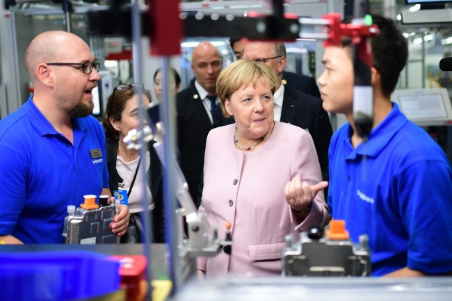 German Chancellor Angela Merkel (C) talks to staff at the company Webasto during a visit in Wuhan, China, 07 September 2019. German Chancellor Angela Merkel is on a visit to China from 06 to 07 September 2019. [Photo: EPA via IC/CLEMENS BILAN]