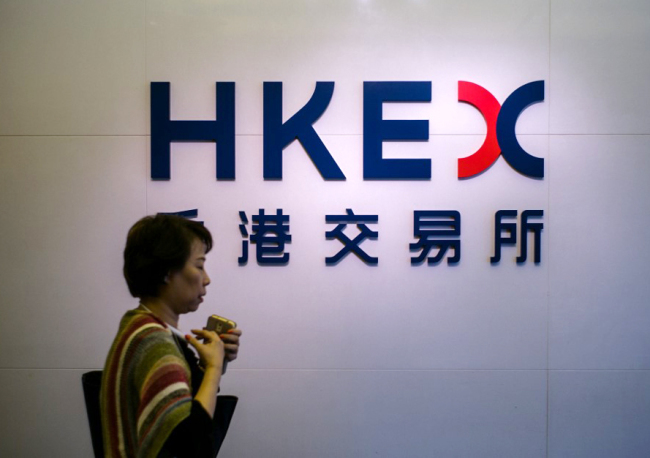 A woman walks past signage for the Hong Kong Exchanges and Clearing Limited (HKEX) outside the stock exchange in Hong Kong on November 17, 2016. [File Photo: AFP]
