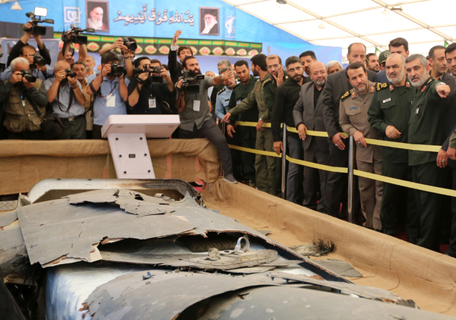 Iranian Revolutionary Guards commander Major General Hossein Salami (2-R) and General Amir Ali Hajizadeh (R) head of Iran's Revolutionary Guards aerospace division, looks at debris from what Iran presented as a downed US drone reportedly recovered within Iran's territorial waters, at Tehran's Islamic Revolution and Holy Defence museum during the unveiling of an exhibition of what Iran says are US and other drones captured in its territory, in Tehran on September 21, 2019. [Photo: AFP/Atta Kenare]