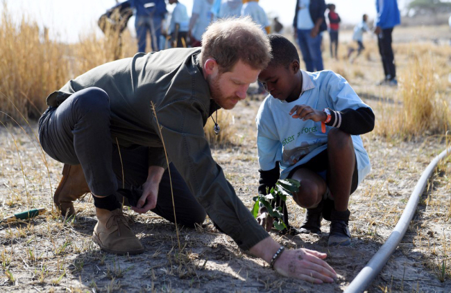 Prince Harry, the Duke of Sussex, helps local school children to plant trees at the Chobe Tree Reserve in Chobe district, in the Northern Botswana on September 26, 2019. [Photo: AFP/Monirul Bhuiyan]