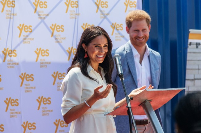 Meghan, Duchess of Sussex (L), is watched by Britain's Prince Harry, Duke of Sussex(R) as she delivers a speech at the Youth Employment Services Hub in Tembisa township, Johannesburg, on October 2, 2019. [Photo: AFP/Michele Spatari]