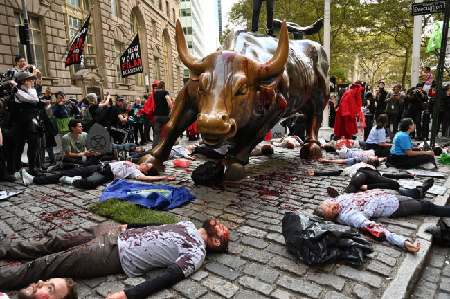 "Protestors covered in fake blood gather around the Wall Street Bull during an ""Extinction Rebellion"" demonstration in New York on October 7,2019. [Photo: AFP]"