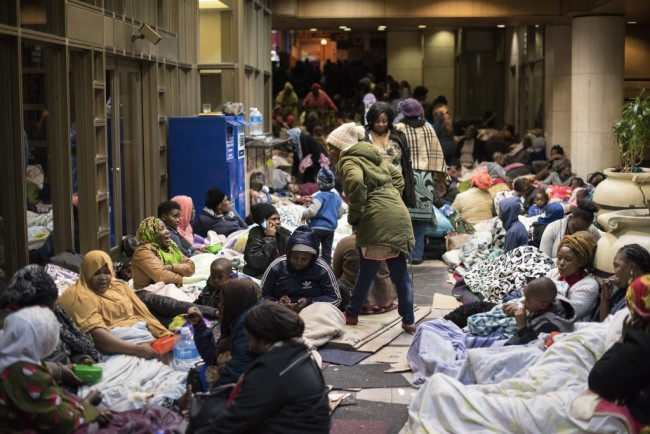Dozens of people camp in a corridor close to the offices of the United Nations High Commission for Refugees (UNHCR) on October 9, 2019 in Cape Town, demanding to be removed from South Africa saying they were no longer safe. [Photo: AFP]
