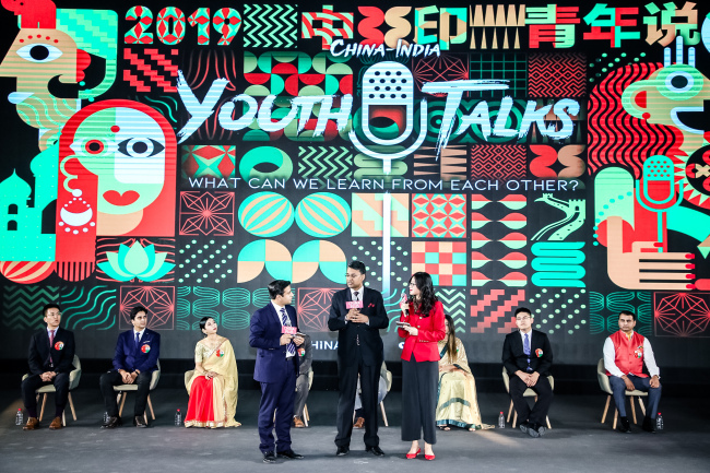 """Zhou Heyang and Akhil Parashar from China Media Group speak to Prasanna Shrivastava (middle), the political counselor at the Embassy of India in China, at """"China-India Youth Talks 2019"""" in Beijing on September 28, 2019. [Photo: China Plus]"""