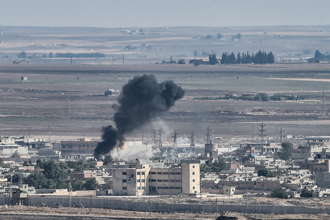 This picture taken on October 13, 2019 from the Turkish city of Ceylanpinar shows smoke rising from the Syrian border town of Ras al-Ain as fighting rages along the border on the fifth day of a Turkish offensive in Syria against the Kurdish People's Protection Units (YPG) that has provoked an international outcry and left dozens of civilians and fighters dead. [Photo: AFP/Ozan Kose]
