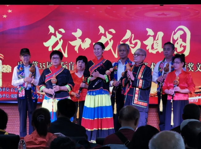 Yang Jia (L4), Li Shiming (R3) and Li's cucurbit flute team perform at a White Cane Safety Day event in Beijing, on October 11, 2019. [Photo: China Plus]