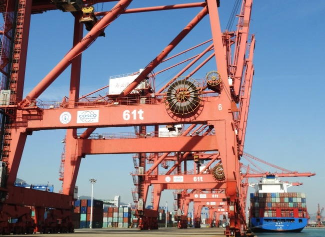 A crane vehicle lifts a container to be shipped abroad from a truck on a quay at the Port of Lianyungang in Lianyungang City, east China's Jiangsu Province, May 8, 2019. [File Photo: IC]