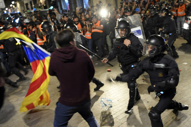 Police clashes with protesters during a demonstration called by the local Republic Defence Committees (CDR), outside the Spanish police headquarters in Barcelona, on October 26, 2019. [Photo: AFP]