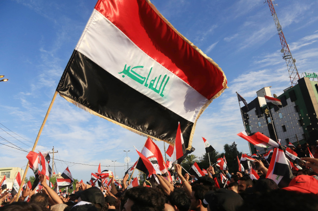 Iraqi protestors wave national flags during a demonstration in the Shiite shrine city of Karbala, south of Iraq's capital Baghdad, on October 25, 2019. [Photo: AFP]