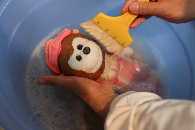 This undated photo shows Zhu Boming washing(清洗 qīngxǐ) a toy at the toy hospital in Shanghai.[Photo: IC]