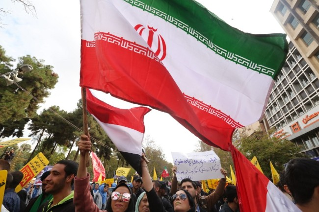 Thousands of Iranian protesters wave national flags during a demonstration outside the former US embassy in the Iranian capital Tehran on November 4, 2019. [Photo: AFP/ ATTA KENARE]