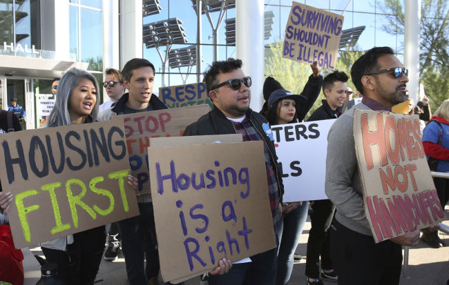 Protesters shout as they hold signs outside Las Vegas City Hall during a protest against the city council's ban on homeless camping on Wednesday, Nov. 6, 2019. [Photo: AP]