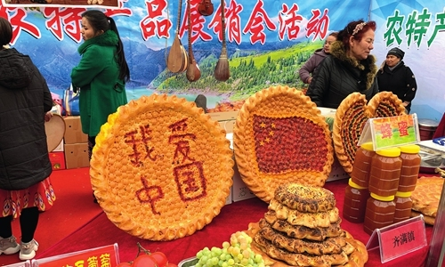 Agricultural products and king-sized pies are displayed at a trade fair in Kuqa County, Xinjiang, on Saturday. [Photo: Li Xuanmin/GT]