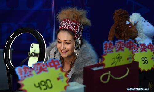 A live-broadcast consultant promotes agricultural products for a company at a fair in a gymnasium in Altay, northwest China's Xinjiang Uygur Autonomous Region, Nov. 27, 2019. The 14th Xinjiang Winter Tourism Trade Fair opened here on Wednesday. [Photo: Xinhua/Sadat]