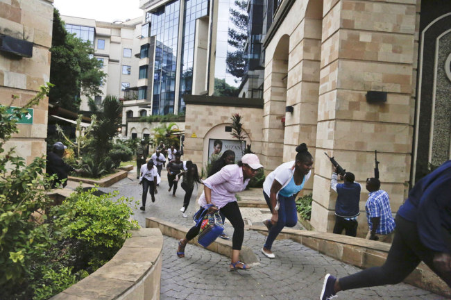 In this Jan. 15, 2019 file photo, people flee as security forces aim their weapons during a deadly attack by extremists at a luxury hotel complex in Nairobi, Kenya. [Photo: AP]