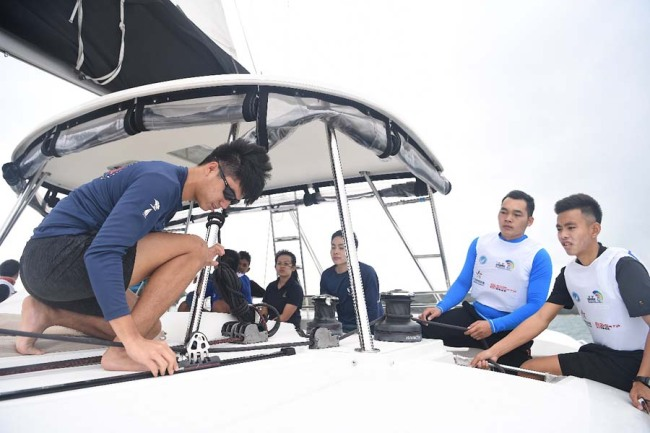Teenager contestants work on their boats during the Belt and Road International Regatta Singapore station on Jan 4, 2019. [Photo provided to China Plus]