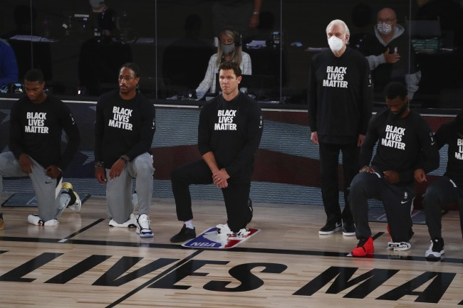 San Antonio Spurs head coach Gregg Popovich, fourth from left, stands while wearing a mask while Sacramento Kings head coach Luke Walton, center, kneels with players before an NBA basketball game Friday, July 31, 2020, in Lake Buena Vista, Fla. [Photo: AP]